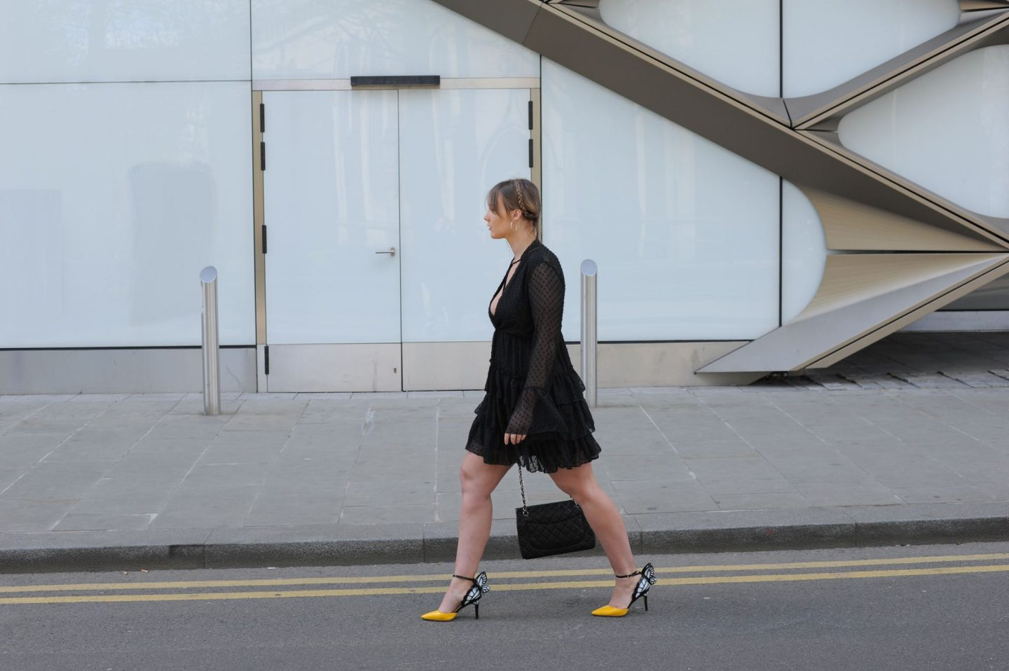 hannah mccreesh crosses road wearing melanie ruffle tiered spot skater dress sophia webster yellow heels chanel bag