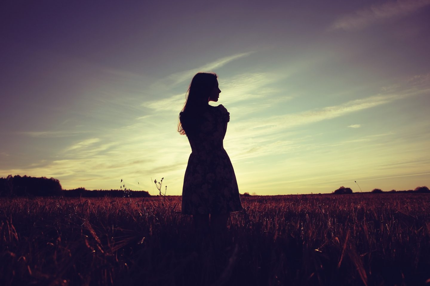 A woman standing in a field at sunset with her back to us looking over to the right
